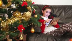 Child girl using tablet pc near Christmas tree Stock Footage