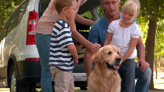 Happy family with their dog in the park - stock footage