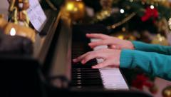 Girl with green playing piano near Christmas tree Stock Footage