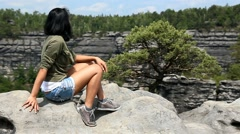Woman tourist sitting on a rock on the lookout Stock Footage