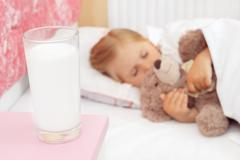 Adorable little girl sleeping in bed with her teddy bear - stock photo