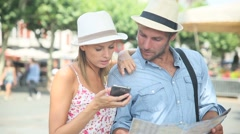Couple of tourists looking at map in city square Stock Footage