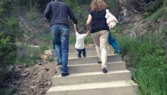 Happy family with little child walk on forest path. UHD 4K steadycam stock fo Stock Footage