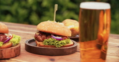 Huge gourmet cheese burgers on a rustic wooden table outdoors - stock footage