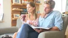 Trendy couple in coffee shop reading magazine sitting in sofa Stock Footage