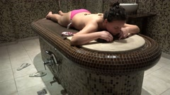 Hot stone massage therapy on a beautiful young Caucasian client. UHD 4K stead Stock Footage