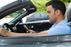 Closeup portrait, young man driving in black gray sports car and checking his - stock photo