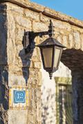 Lantern vintage on the wall of an old stone seafront - stock photo