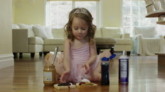 Medium shot of ballerina girl assembling sandwich on floor / Cedar Hills, Utah, Stock Footage