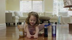 Medium shot of ballerina girl spreading food on floor / Cedar Hills, Utah, Stock Footage