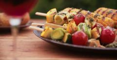 Plate of healthy grilled vegetables on a wooden table outdoors - stock footage