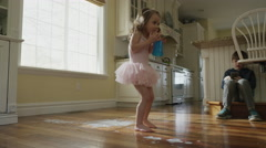 Low angle panning slow motion shot of girl dropping cup on kitchen floor / Cedar Stock Footage