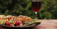 Barbecue grilled vegetable kebabs, corn and asparagus on a plate Stock Footage