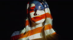 Close up slow motion shot of American flag projection on woman's face / Cedar Stock Footage