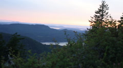 EARLY EVENING SUNSET OVER COASTAL MOUNTAIN ISLANDS AND FOREST Stock Footage