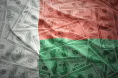 colorful waving madagascar flag on a american dollar money background - stock photo