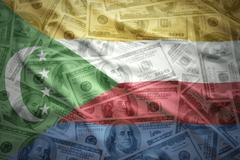 colorful waving comoros flag on a american dollar money background - stock photo