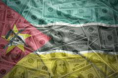 Stock Photo of colorful waving mozambican flag on a american dollar money background