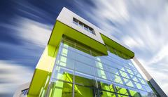 Office building with motion blurred clouds, business concept. Stock Photos