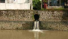 Drainage water outlet in stony bank wall, opaque water Stock Footage
