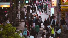 People walk down the street outside Shinjuku station in the rain - stock footage