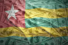 colorful waving togo flag on a american dollar money background - stock photo