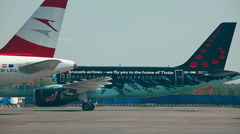 Stock Video Footage of Brussels airlines A320 and Austrian A320 parked on apron