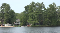 Cottages and boathouses on a tranquil lake Stock Footage