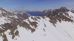 AERIAL: Flying above huge rocky mountains in early spring - stock footage