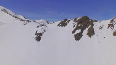 AERIAL: Flying above snowy mountain ski resort in European Alps - stock footage