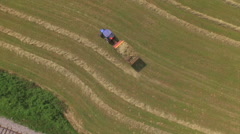 AERIAL: Flying above farmer picking up hay with tractor Stock Footage