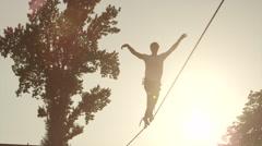 SLOW MOTION: Man walking on high slackline at summer sunset Stock Footage