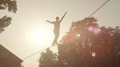 Man balacing on slackline between the houses in big city Stock Footage