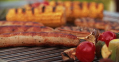 Barbecue grill with sausages, chicken and vegetables being cooked Stock Footage