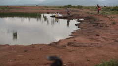 Tribal women collect bad water from savannah puddle, Samburu, Kenya, Africa Stock Footage