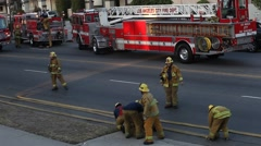 Firemen in action rolling up hoses - stock footage