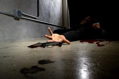 Bloody Male Victim Stabbed in an Alley - stock photo