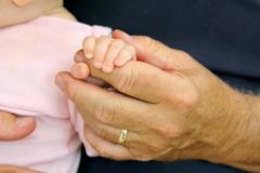 Newborn Baby Girl Holding Grandpa's Hand Stock Photos