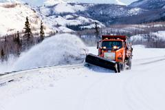 Snow plough clearing road in winter storm blizzard Kuvituskuvat