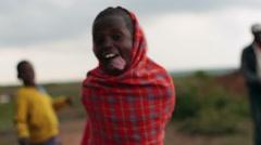 Poor child in red smiles in Samburu, Kenya, Africa, close up Stock Footage