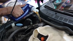 Engine oil flows from the canister into the engine of a car in service - stock footage