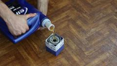 Auto mechanic pours motor oil into the oil filter before installing Stock Footage