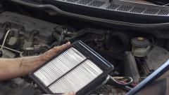 Auto mechanic installs the engine air filter and closes the cover Stock Footage
