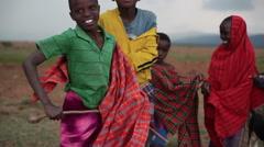 Colorful traditional Samburu children jump and play, Kenya, Africa, medium shot Stock Footage