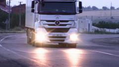 A truck rides with a light on. Headlights reflected on the asphalt. - stock footage