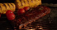 Tender ribs, tomatoes and corn grilling on a barbecue Stock Footage