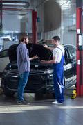 Customer talking with automobile mechanic Stock Photos