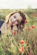 Beautiful woman is smiling and posing in poppy flowers field Stock Photos