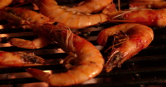 Prawns with spicy seasoning grilling on a barbecue at night Stock Footage