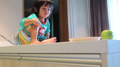 A little asian girl with breakfast in kitchen and watching cartoon on tablet Stock Footage